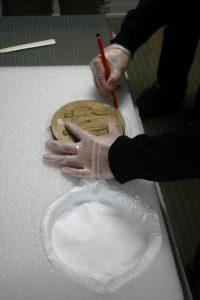 Fabrication d'un plateau en mousse pour le conditionnement d'un bas-relief en plâtre.